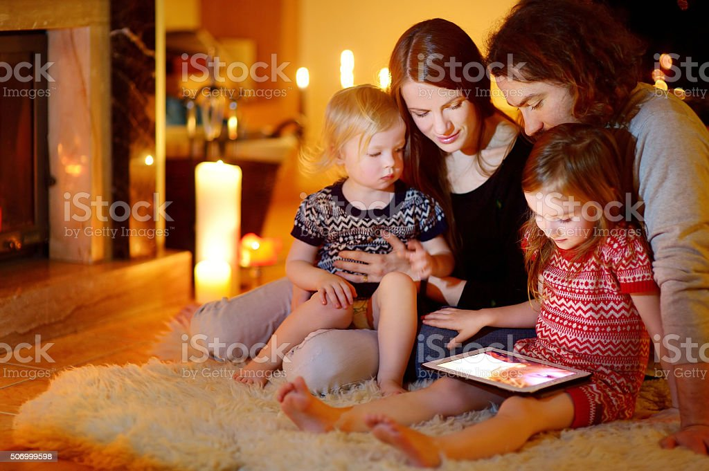 Happy family using tablet pc by a fireplace stock photo