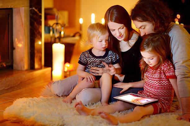 glückliche familie mit tablet pc mit offenem kamin - kinder weihnachtsfilme stock-fotos und bilder