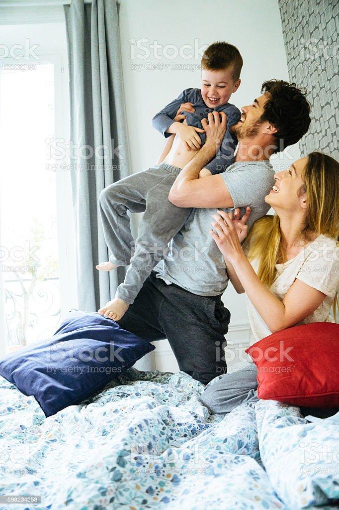 Família feliz de acordar de manhã, jogando na cama foto royalty-free