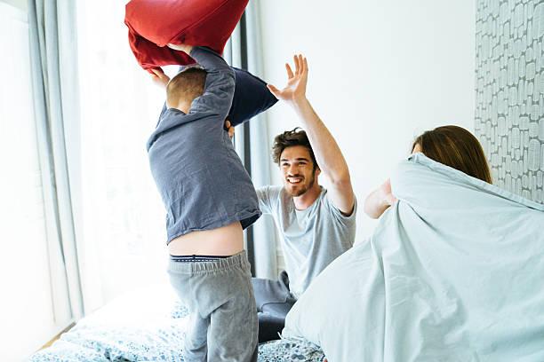 glückliche familie aufwachen am morgen, spielen im bett - kissenschlacht paar stock-fotos und bilder
