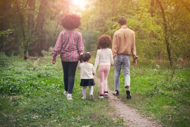gelukkige familie wandelen langs een pad in het bos - bos spelen stockfoto's en -beelden
