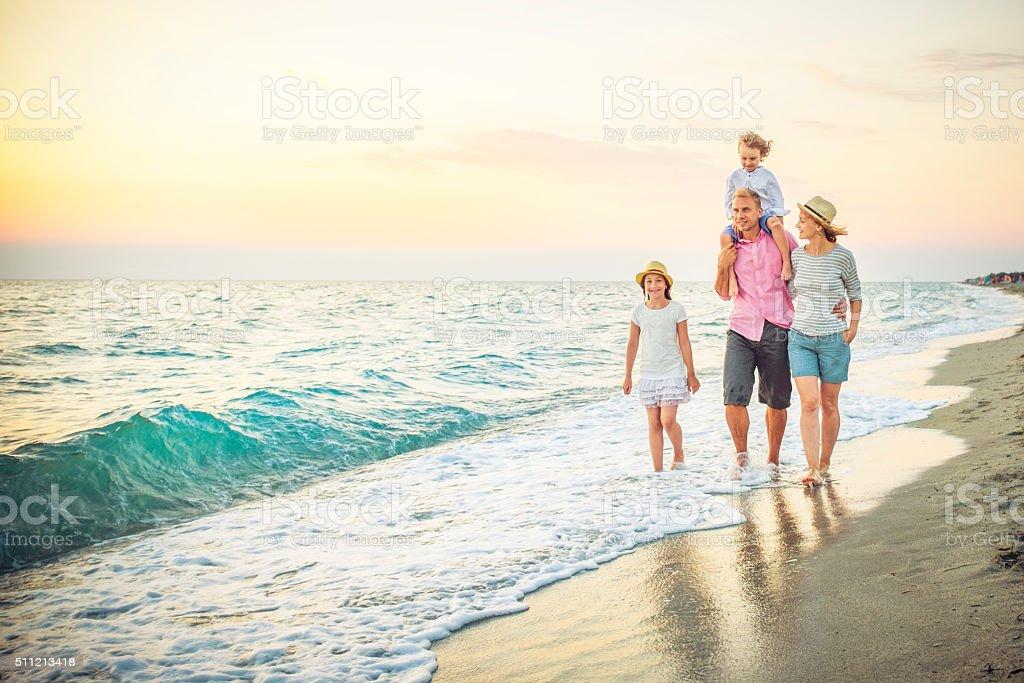 Famille heureuse marchant le long d'une plage de sable blanc - Photo