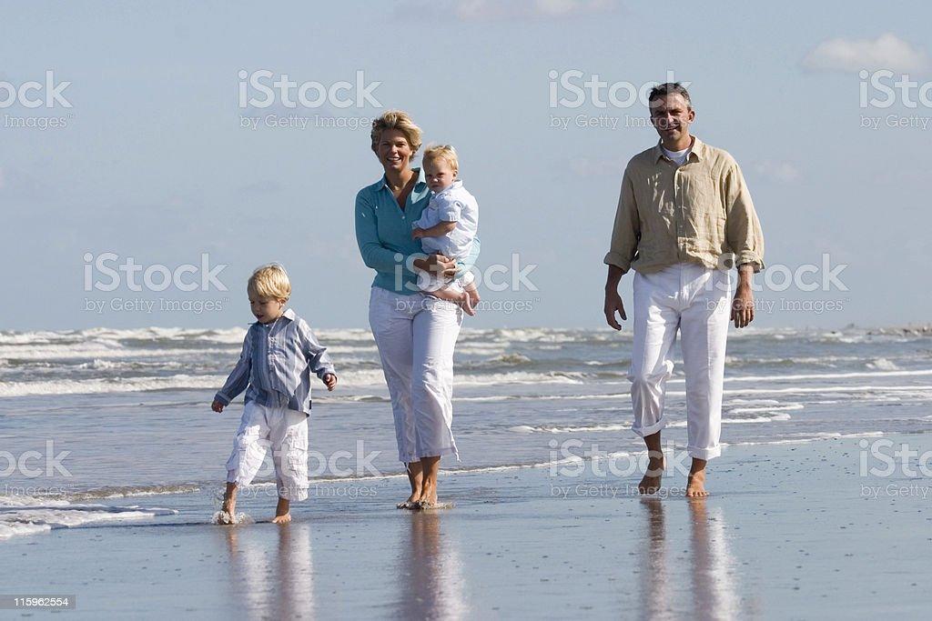 happy family walking along the beach royalty-free stock photo