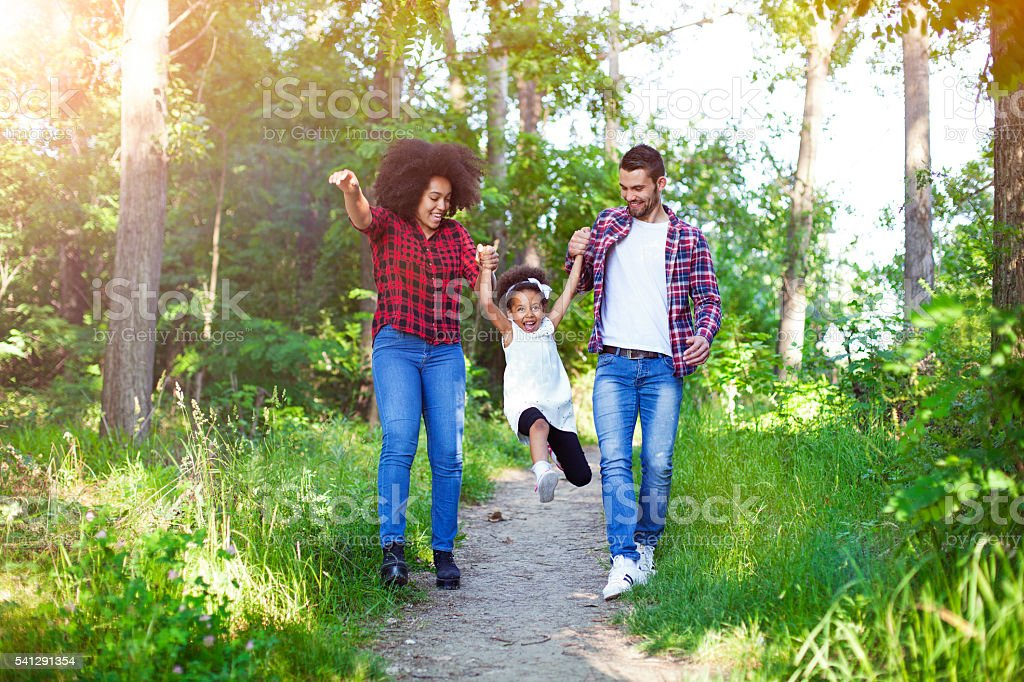 Happy family walking and swinging their daughter. stock photo
