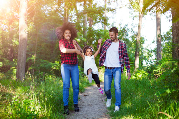happy family walking and swinging their daughter. - african youth jumping for joy stock photos and pictures