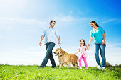 Cheerful family taking a walk in the meadow with their golden retriever dog.
