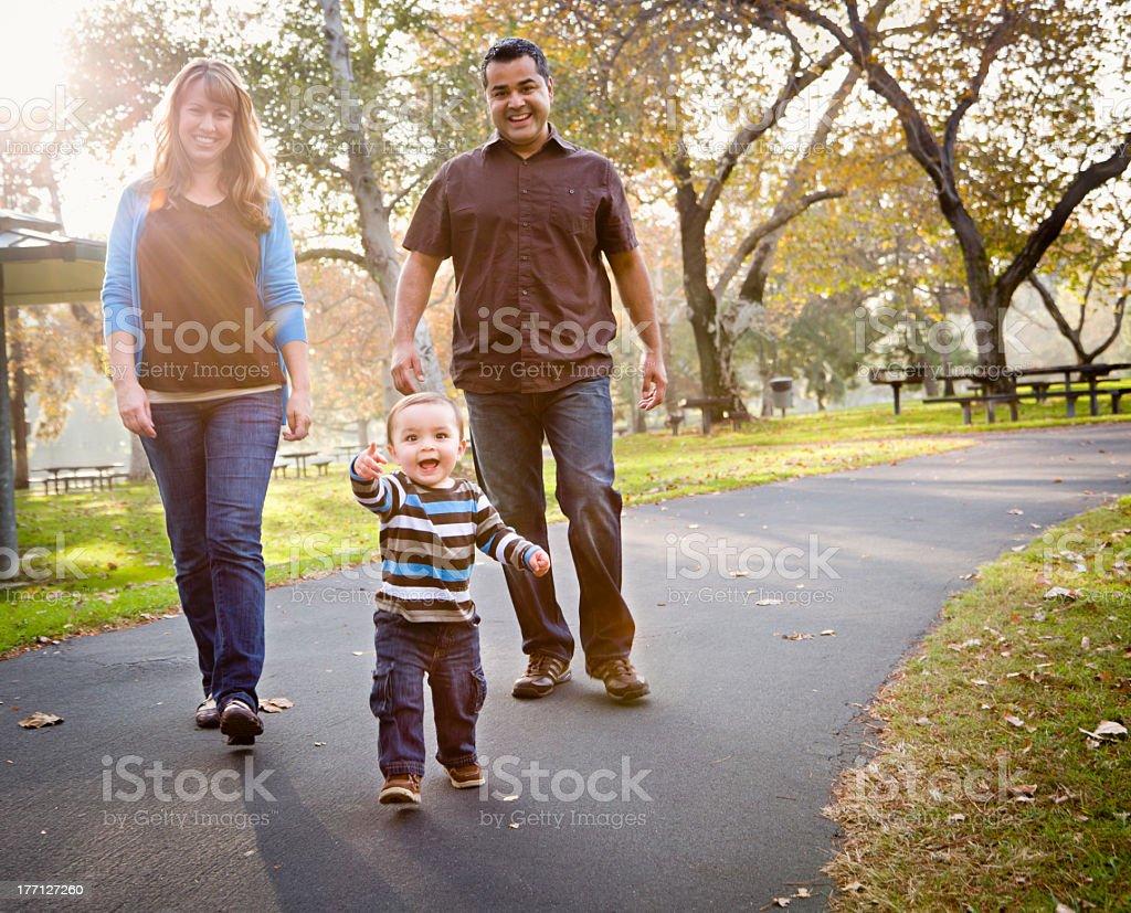 Happy family walking down the park street stock photo