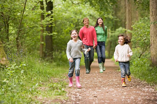 happy family walking on a path in the woods - bos spelen stockfoto's en -beelden