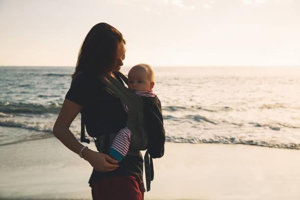 Familia feliz caminando en aire libre de la naturaleza. Niño en una mochila de portador. - foto de stock