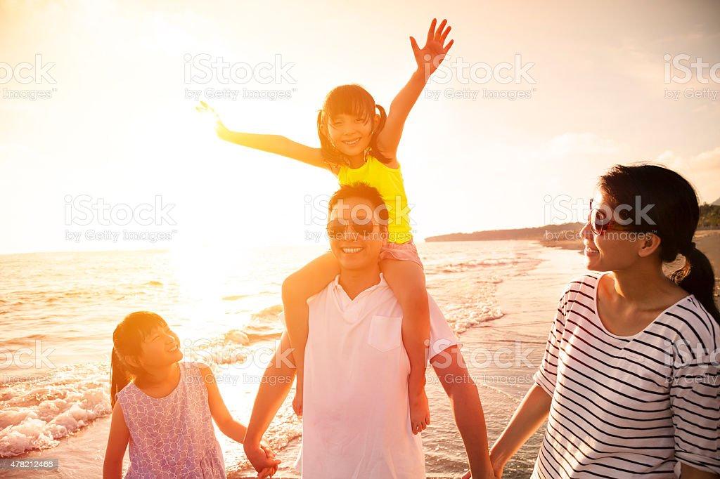 happy family walking on the beach stock photo