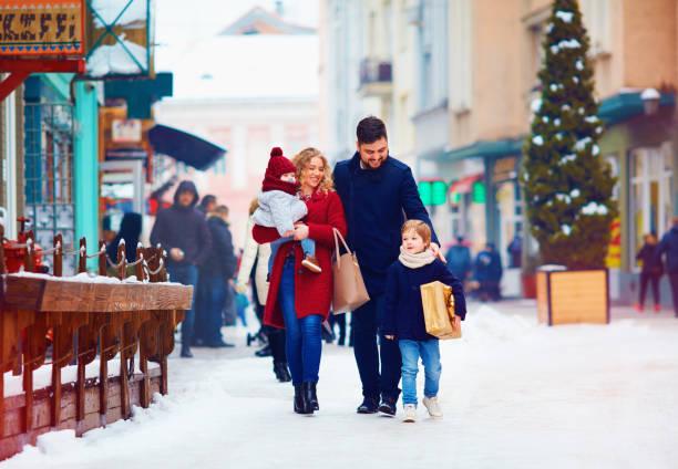glückliche familie zu fuß zusammen, in der verschneiten stadt straße während der winterferien - festliche babymode junge stock-fotos und bilder