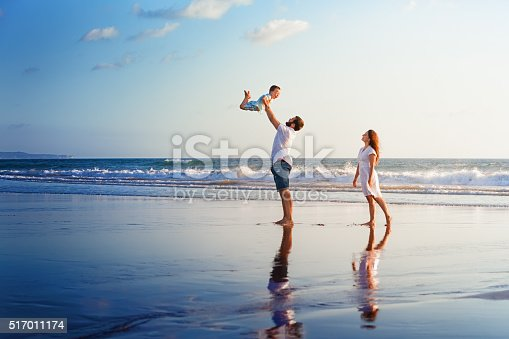 istock Happy family walking with fun on sunset sea beach 517011174
