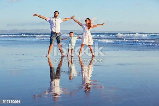 istock Happy family walking with fun on sunset sea beach 517110564