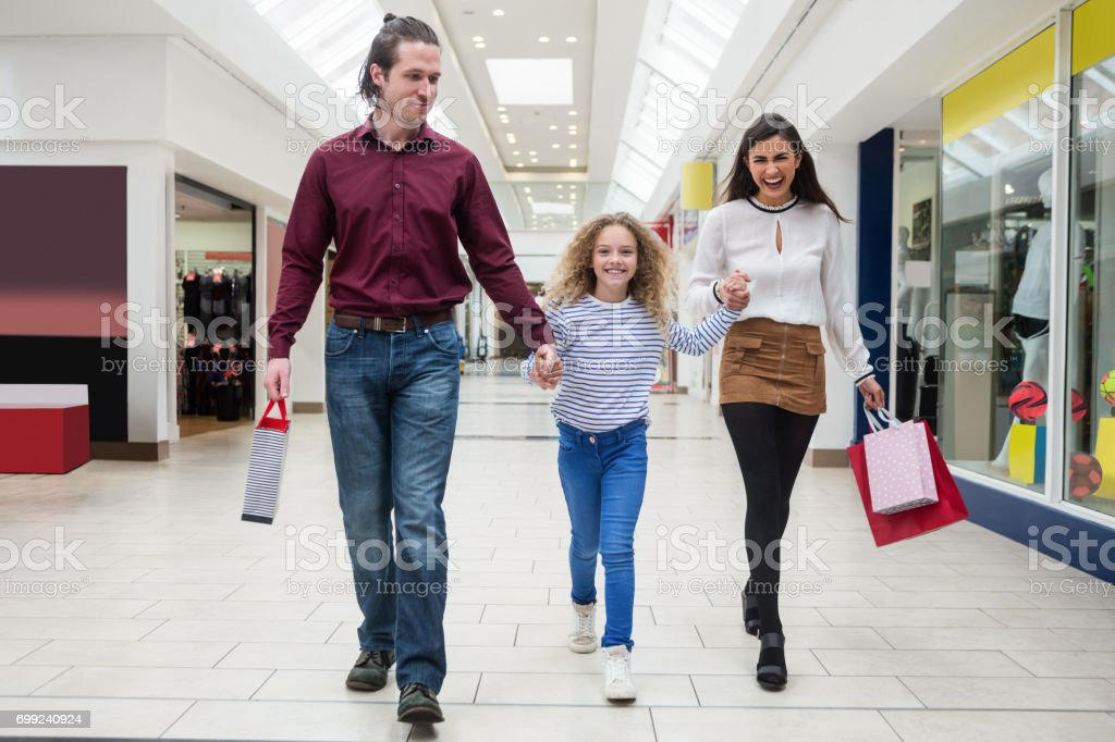 Happy family walking with shopping bags stock photo