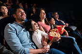 Happy Latin American family watching a comedy film at the cinema and laughing - entertainment concepts