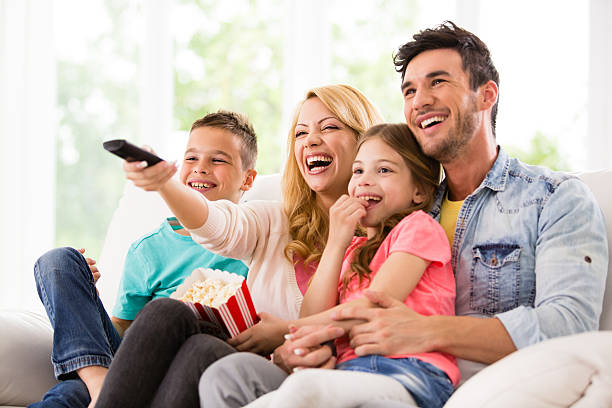 happy family watching tv and eating popcorn - family watching tv stock photos and pictures