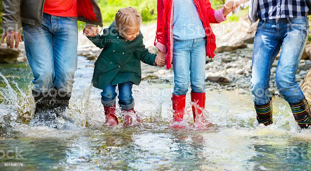 Happy family wearing rain boots jumping into a mountain river - foto stock