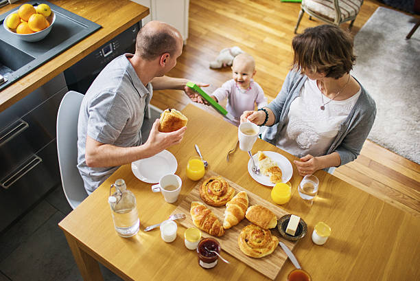 Happy Family With A Child Eating French Breakfast At Home Stock Photo