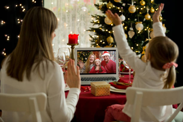 A happy family with a child is celebrating Christmas with their friends on video call using webcam stock photo