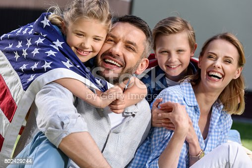 istock Happy family with american flag hugging outdoors, Independence Day concept 802429244
