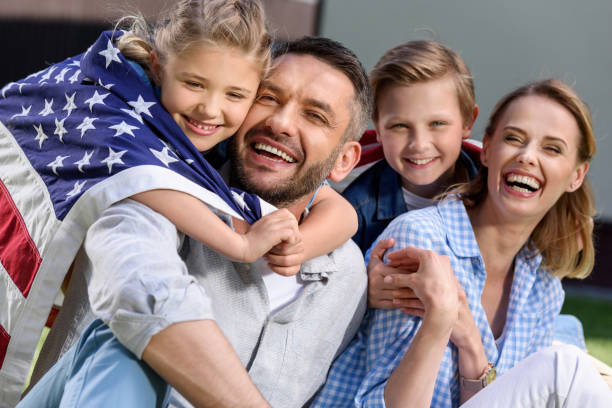 Happy family with american flag hugging outdoors, Independence Day concept stock photo