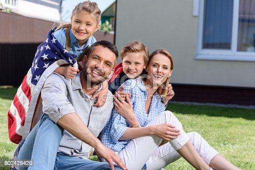 istock Happy family with american flag hugging outdoors, Independence Day concept 802429420