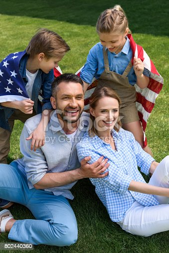 istock Happy family with american flag hugging outdoors, Independence Day concept 802440360
