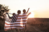 Happy family, dad and daughter holding the American flag at sunset. Dressed in white. The concept of family values and friendship . Patriotic feeling.