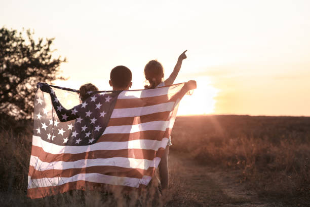 A happy family with an American flag at sunset. Happy family, dad and daughter holding the American flag at sunset. Dressed in white. The concept of family values and friendship . Patriotic feeling. patriotism stock pictures, royalty-free photos & images