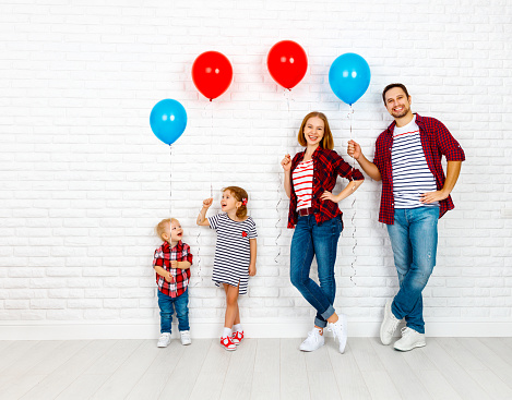 Happy family with ballons. mother, father, son, daughter on a white blank wall