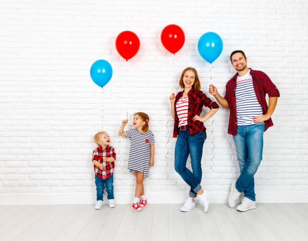 Happy family with ballons. mother, father, son, daughter on a white blank wall stock photo