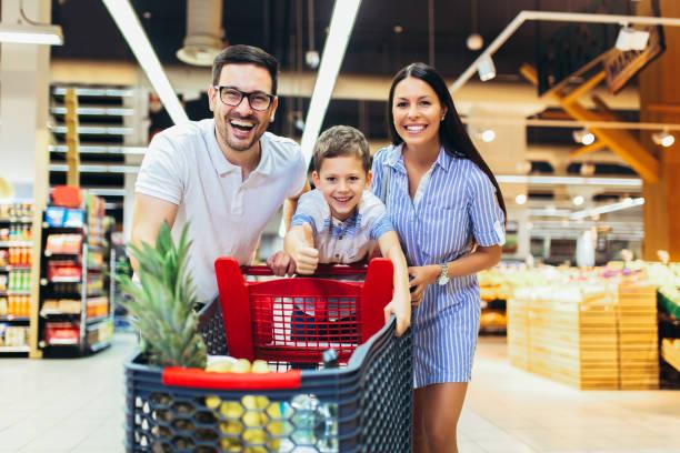 Familia feliz con el niño y carrito de la compra comprando alimentos en la tienda de comestibles o supermercado - foto de stock