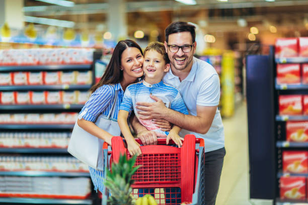 Happy family with child and shopping cart buying food at grocery store or supermarket stock photo