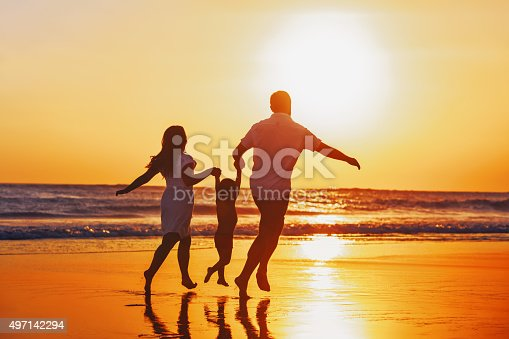 Happy family - father, mother, baby son hold hands and run with fun along edge of sunset sea on black sand beach. Active parents and people outdoor activity on tropical summer vacations with children.