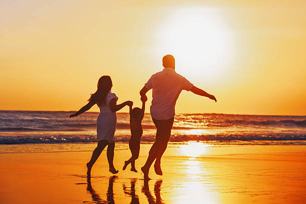 Happy family with child have a fun on sunset beach stock photo