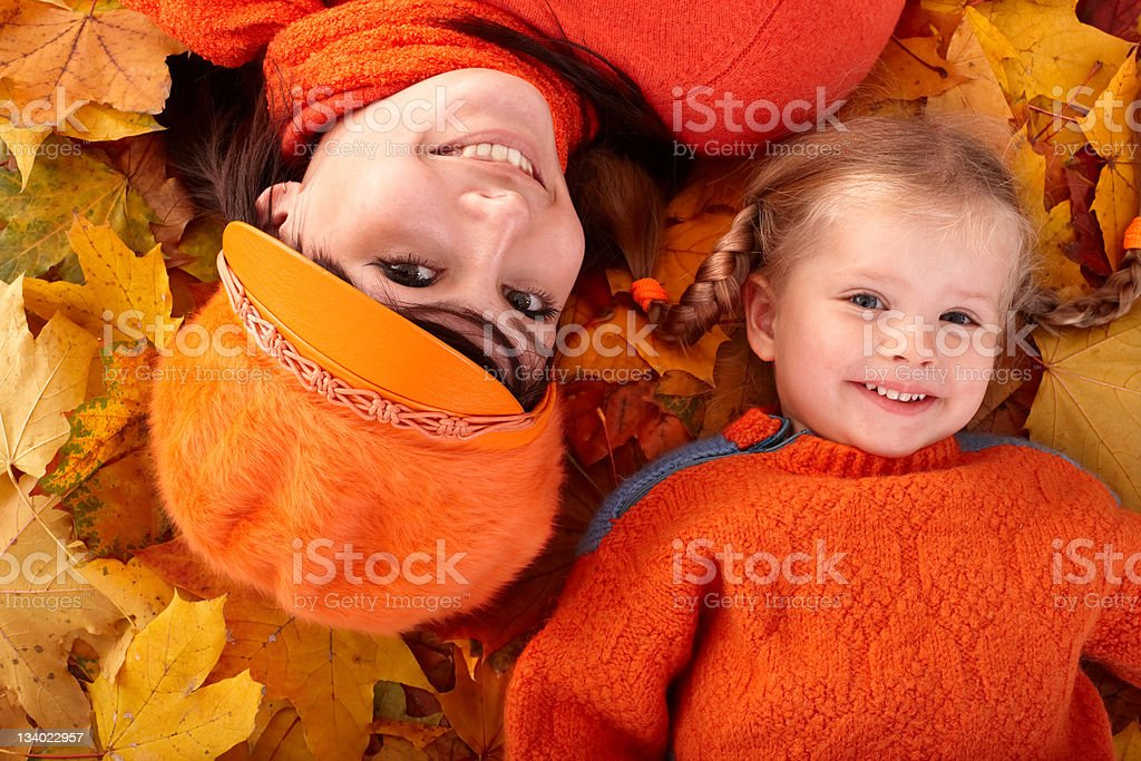 Happy family with child on autumn orange leaves. royalty-free stock photo