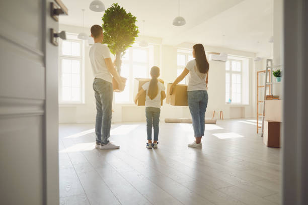Happy family with children moving with boxes in a new apartment house. Back view. stock photo