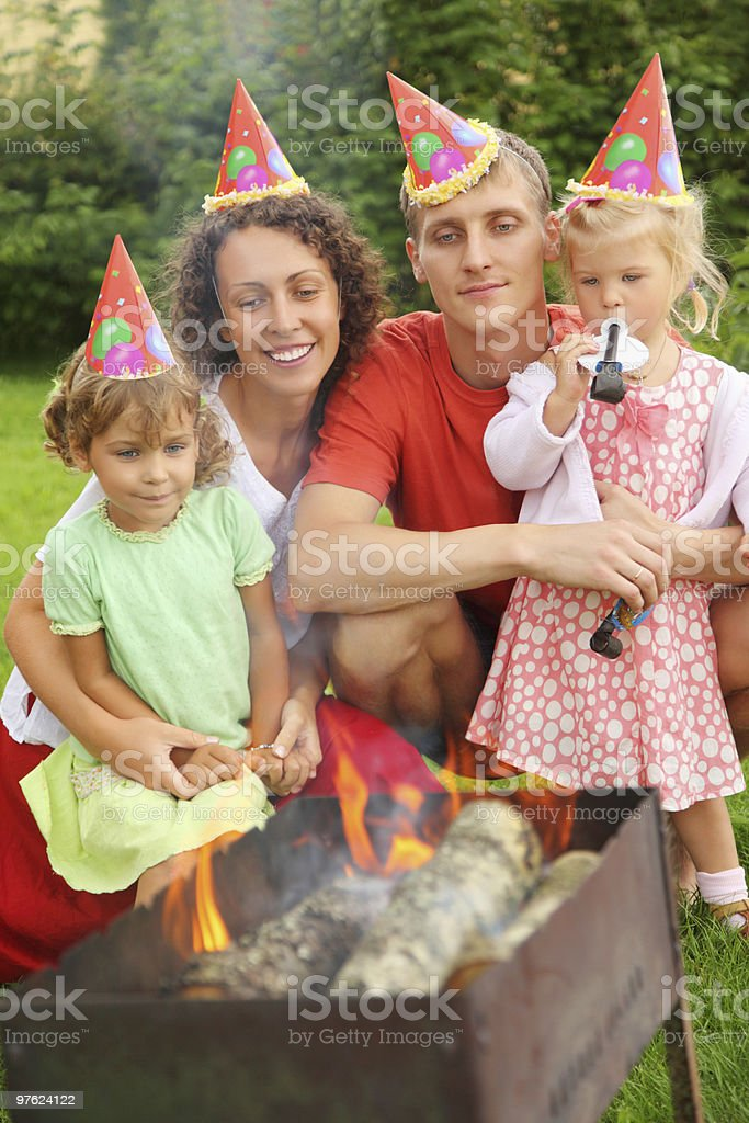 Happy family with children near brazier on picnic royalty-free stock photo