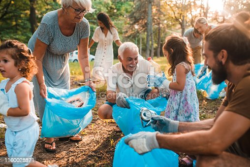Happy family with children collecting trash and recycling