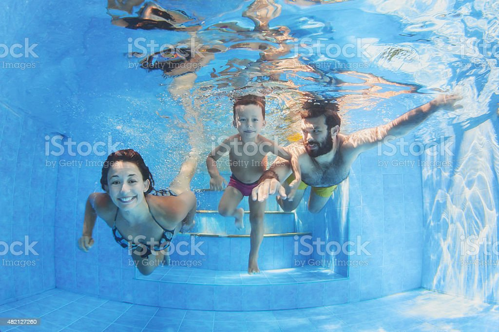 Happy family with children swimming with fun in pool stock photo
