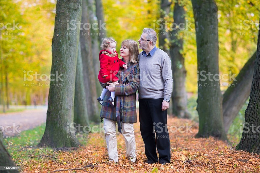 Happy family with cute toddler girl walking in autumn park stock photo
