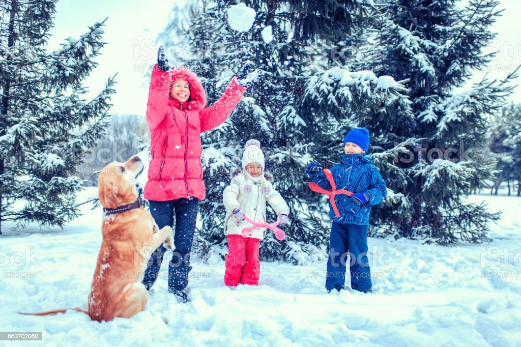 happy family with dog in winter park stock photo