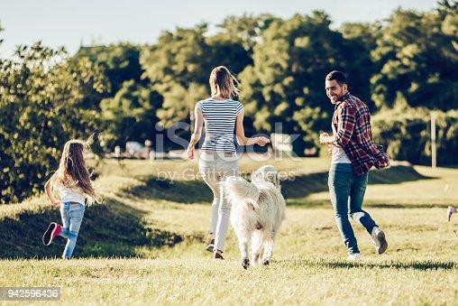 942596618 istock photo Happy family with dog 942596436