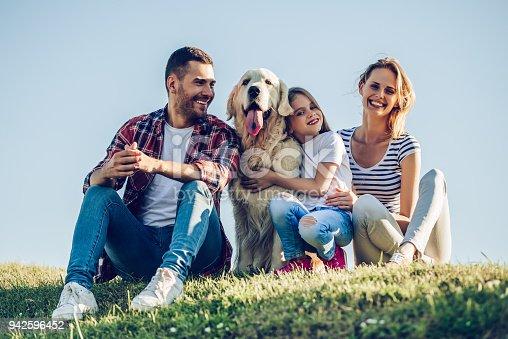 942596618 istock photo Happy family with dog 942596452