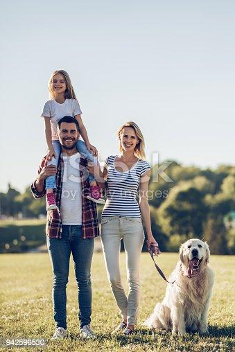 942596618 istock photo Happy family with dog 942596530
