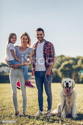 942596618 istock photo Happy family with dog 942596540