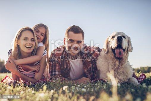 942596618 istock photo Happy family with dog 942596624
