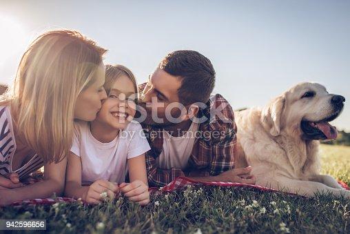 942596618 istock photo Happy family with dog 942596656