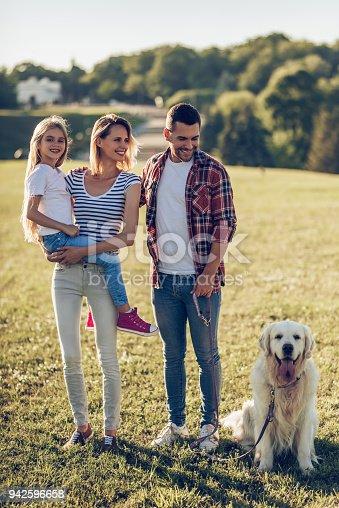942596618 istock photo Happy family with dog 942596658