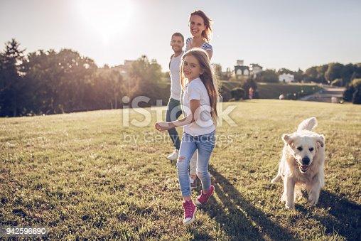 942596618 istock photo Happy family with dog 942596690